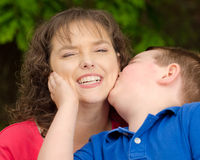Happy mother smiling at kiss from son Stock Photos
