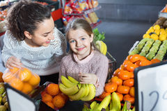 Happy  mother and smiling little girl choosing fresh fruits Royalty Free Stock Images