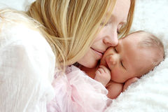 Happy Mother Snuggling Newborn Baby in Bed Royalty Free Stock Photo