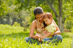 Happy mother and son. Sitting in a meadow Stock Photos