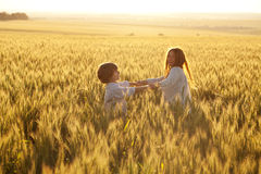 Happy mother and son. Are running through a wheat field in summer Stock Photos