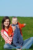 Happy mother with son. Sitting on green grass stock image