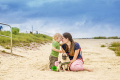 Happy mother and son at the beach. Mother with son and pug at the beach Royalty Free Stock Photo