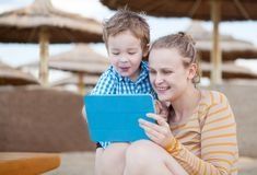 Happy mother and son at a beach resort. Happy mother and her small son at a beach resort playing on a tablet computer together under beach umbrellas at the stock photos