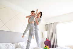 Happy mother with son in bed at home or hotel room Royalty Free Stock Photos