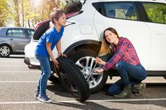 Happy mother and son changing flat tire together royalty free stock image