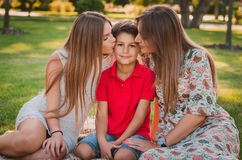 Happy mother, son and daughter in the park. Mom and sister kiss their son. Happy family concept.  Stock Photos