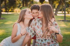 Happy mother, son and daughter in the park. Mom and sister kiss their son. Happy family concept. Happy mother, son and daughter in the park. Mom and sister kiss Royalty Free Stock Photography