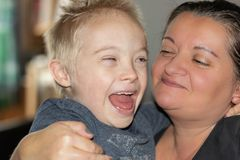 Defect,childcare,medicine and people concept. Happy mother and son with down syndrome together at home royalty free stock image