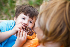 Happy mother with son eating cocoa snail Stock Images