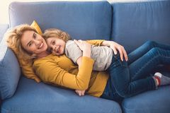 Happy mother and son are embracing on couch. Cheerful family is lying on divan in living room and hugging each other. They are looking at camera and smiling Stock Photos