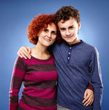 Happy mother and son embracing each other. Studio shot of a happy mother and son embracing each other stock images