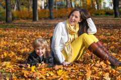 Happy mother and son enjoying in autumn. Portrait of happy mother and son relaxing in the park and enjoying in autumn season royalty free stock photo