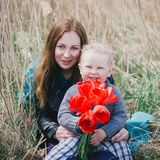 Happy mother and son with flowers. Smiling mother and her little son with red tulips Stock Image