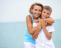 Happy mother and son having fun on the beach. Royalty Free Stock Photography