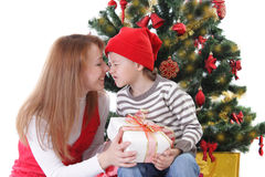 Happy mother and son having fun under Christmas tree Royalty Free Stock Images