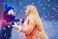 Happy mother and son having fun under winter snow Royalty Free Stock Photography