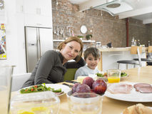 Happy Mother And Son Having Meal At Dining Table. Portrait of happy mother and son having meal at dining table in kitchen stock images