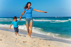 Happy mother with son holding arms and running. Together during sunny day on beach coast and near ocean waves royalty free stock images