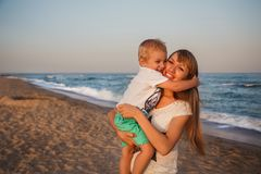 Happy mother and son hugging at beach.  royalty free stock photos