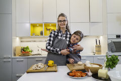 Happy mother and son hugging in the kitchen. Royalty Free Stock Images