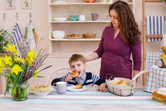 Happy mother and son in the kitchen. Mother and son having breakfast. Happy mother and son in the kitchen. Concept of happy family and healthy food. Boy eating royalty free stock image