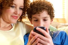 Happy mother and son looking at mobile device Stock Photos