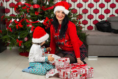 Happy mother and son open Christmas gifts Royalty Free Stock Photos