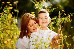 Family happy outdoors. Happy mother and son in the park. Beauty nature scene with family outdoor lifestyle. Happy family eating together on the green grass stock image