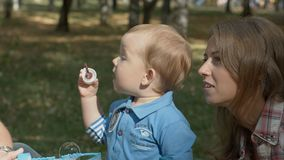 Happy mother and son in the park blowing soap bubbles outdoor portrait. Shot on BMCC. You can use it e.g in your video, documentalistic, reporting Royalty Free Stock Image