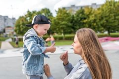 Happy mother and son, play laughing and smiling, on summer day park autumn, casual wear jeans and baseball cap, care and