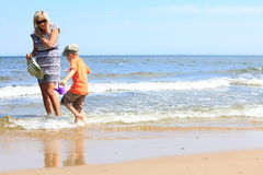Happy mother and son playing on beach Stock Photo