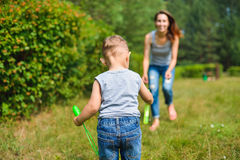Happy Mother and son playing with bubbles at summer day Royalty Free Stock Photo