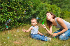Happy Mother and son playing with bubbles at summer day Stock Photo