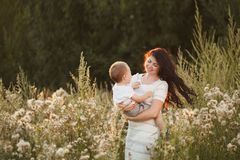 Happy mother and son playing in the field stock photo