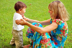 Happy mother and son playing on the grass Royalty Free Stock Images
