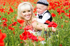 Happy mother and son on the poppies field Stock Image