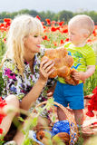 Happy mother and son on the poppies field Royalty Free Stock Images