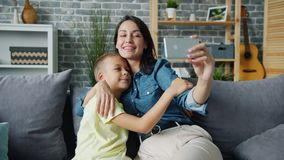 Happy mother and son posing for smartphone camera hugging smiling taking selfie. Happy mother and son are posing for smartphone camera hugging smiling taking stock footage