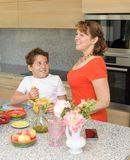 Happy mother and son preparing lunch with a mortar stock photo