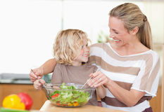 Happy mother and son preparing salad Stock Photo