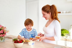 Happy mother and son preparing snacks in the morning at home kitchen Royalty Free Stock Photography