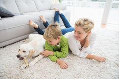Happy mother and son with puppy. At home in the living room royalty free stock photo