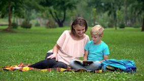 Happy mother and son reading book outdoors, common interest, leisure time. Stock photo stock photos