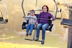 Happy mother and son ride chair lift Stock Photos