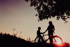 Happy mother and son riding bike at sunset Royalty Free Stock Images