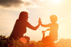 Happy mother and son riding bike at sunset Stock Images