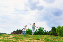 Happy Mother and son running on grass smiling Royalty Free Stock Photography