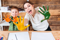 Happy mother and son showing painted hands in colorful paint Royalty Free Stock Photos