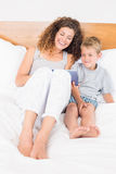 Happy mother and son sitting on bed with tablet pc stock photo